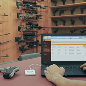 A Armorer Logbook Universal in a computer. Background is an armory with a lot of guns.