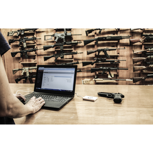 A person using a computer with the Armorer Logbook app. NFC device is in the table with a firearm. The location of the picture is in an armory