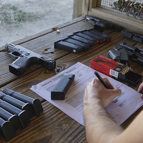 A table in a Shooting Range with a glock with a Smart Slide, bullets and some magazines.